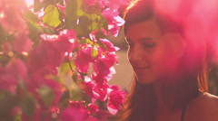 A close up of cute young woman looking at flowers with a sexy look Stock Footage