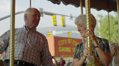 Close up of senior couple riding carousel at carnival / American Fork, Utah, Stock Footage