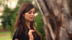 A cute young woman walks past a tree looking into the camera with a sexy look Arkistovideo