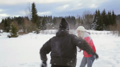 A young couple have a snowball fight and wrestle n a covered field of snow - stock footage