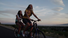 Tracking medium shot of young women riding tandem bicycle on road / Cedar Hills, - stock footage