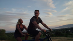 Tracking medium shot of couple riding tandem bicycle on road / Cedar Hills, Stock Footage