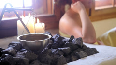 A close up of a woman putting water on the rocks in a sauna Stock Footage