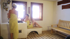 Two young women sit inside a sauna Stock Footage