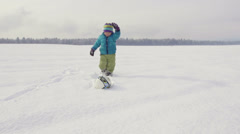 Slow-Mo: Little Boy Kicks Soccer Ball On Snow Covered Field - stock footage