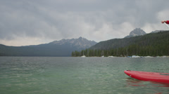 Wide shot of young woman paddleboarding on lake / Redfish Lake, Idaho, United - stock footage