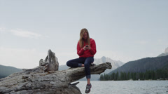 Medium shot of young woman using cell phone on log at lake / Redfish Lake, Stock Footage