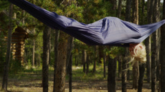 Medium shot of girl spinning in hammock in forest / Idaho, United States Stock Footage