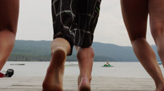 Medium shot of friends on dock running and jumping into lake / Redfish Lake, Stock Footage