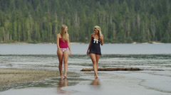 Wide shot of young women wading in lake / Redfish Lake, Idaho, United States Stock Footage