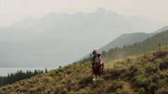 Wide shot of friends horseback riding near lake / Redfish Lake, Idaho, United Stock Footage