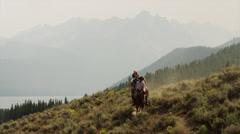 Wide shot of friends horseback riding near lake / Redfish Lake, Idaho, United Stock Footage