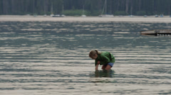 Medium shot of girl playing in lake / Redfish Lake, Idaho, United States Stock Footage