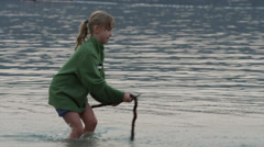Medium shot of girl playing with stick in lake / Redfish Lake, Idaho, United Stock Footage