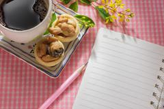 Notebook on table with cup of coffee and dessert. Stock Photos