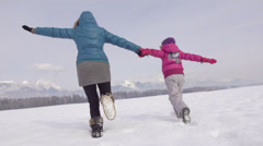 Slow-Mo: Mother And Daughter Running Over Snow Covered Field Stock Footage