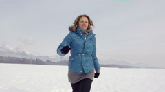 Slow-Mo: Woman Running Over Snow Covered Field Stock Footage