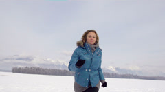 Slow-Mo: Happy Woman Running Over Snow Covered Field Stock Footage