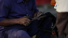 Indian mechanic cuts rubber seal to repair a puncture on the bike next to him - stock footage