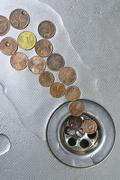 Coins go to drain Stock Photos