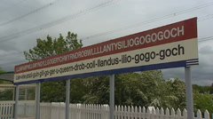 Station sign with  pronunciation guide if Llanfairpwllgwyngyll railway station Stock Footage