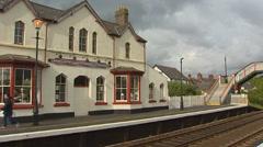 Platform and building Llanfairpwllgwyngyll railway station pan crossing bridge Stock Footage
