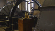 Stock Video Footage of steam engine room, rotating flywheel behind copper oilcans - zoom in