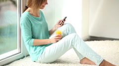 Cheerful girl sitting on floor by window using cellphone drinking juice looking Stock Footage