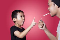 Asian boy ask his father to quit smoking Stock Photos