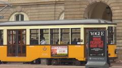 Follow, pan right old yellow tram passing downtown city urban street pedestrian  Stock Footage