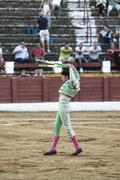 spainish bullfighter with the whitw and green flags high to attract the bull  - stock photo