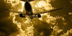Passenger jet landing against amber sky Stock Photos