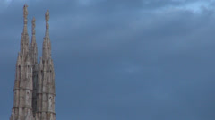 Detail sculpture Milan cathedral church gothic facade among dark clouds twilight Stock Footage