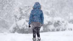 Slow Mo: Young Woman Walking Alone Through Snow Blizzard Stock Footage