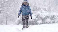 Slow Mo: Young Woman Walking Alone Through Fresh Snow Stock Footage