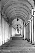 street with the old arcades and the play of light between columns - stock photo