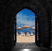 looking through doors towards blue sky beach - stock photo