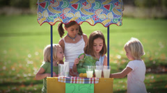 Young girls get their lemonade stand ready by poring lemonade in cups Stock Footage