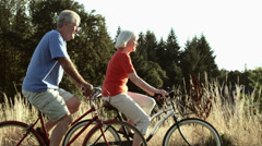 Stock Video Footage of Senior couple enjoy time together bike riding. Wide shot.