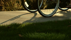 Two older people ride their bikes down the sidewalk as the camera follows them - stock footage