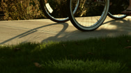 Two older people ride their bikes down the sidewalk as the camera follows them Stock Footage