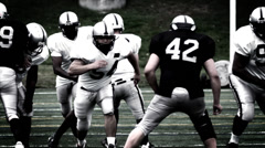 A Running Back receives a handoff and spins to avoid a defender - stock footage