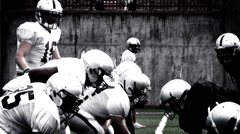 A Quarterback hikes the ball from the line of scrimmage and throws a pass - stock footage