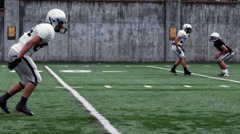 A Running Back receives a handoff and sidesteps and spins passed defenders Stock Footage