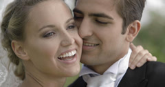 Groom posing with his pretty new wife in a park Stock Footage