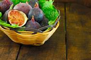 Stock Photo of basket of ripe figs in a basket on bed of leaves