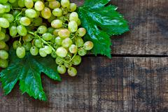 green grapes on a rustic wooden table - stock photo