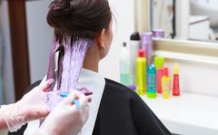 Hairdresser applying color female customer at salon, doing hair dye Stock Photos