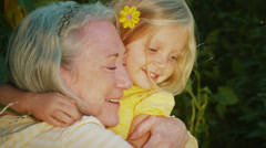 A little blonde girl hugs her grandmother then runs to play in the garden. Stock Footage
