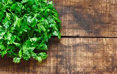 Stock Photo of fresh curly leaf parsley on rustin wooden background